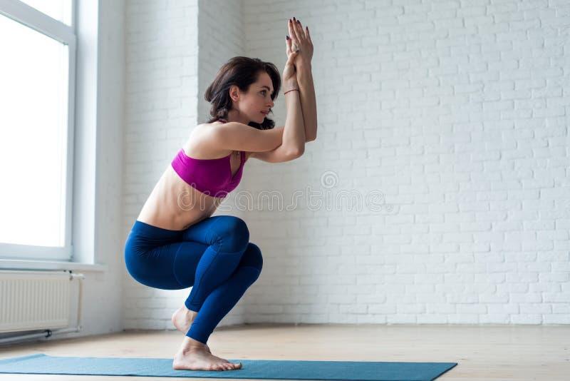 Den tunna flickan i activewearen som gör yogaövningen Garudasana eller Eagle, poserar med kal fot på mattt i sportklubba royaltyfria foton