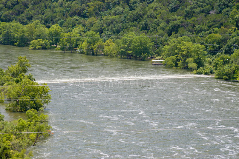 Den turbulenta linjen av vatten över floden är en doppad väg royaltyfri bild