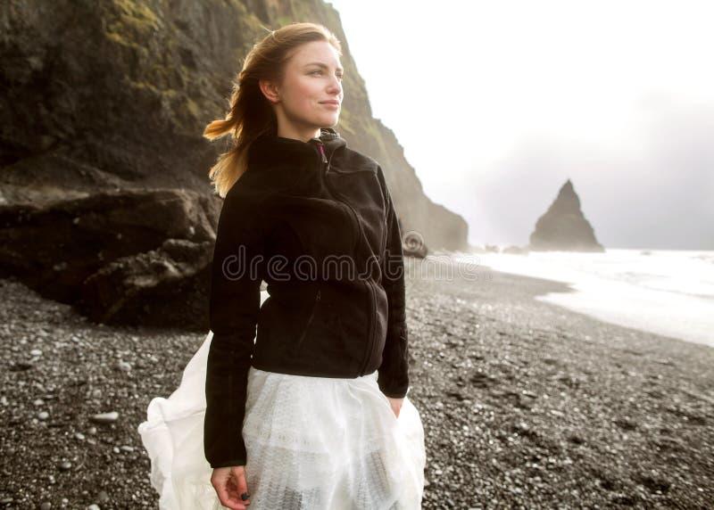 Den turist- flickan står på stranden på solnedgången royaltyfri fotografi