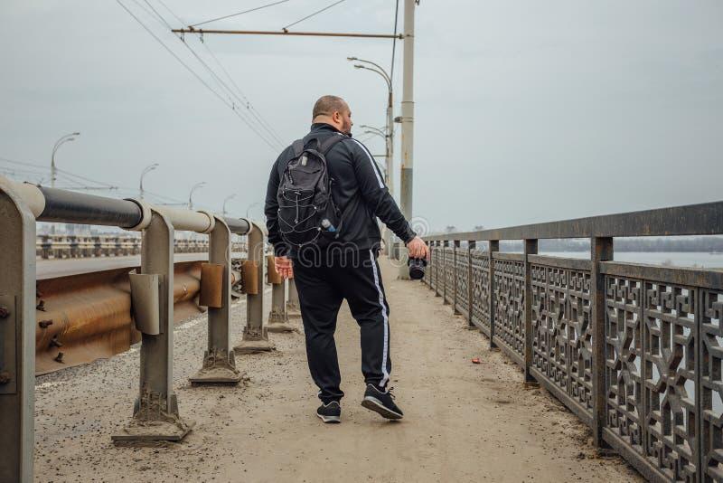 Den turist- fotografen med kameran och ryggsäcken promenerar bron isolated rear view white royaltyfri fotografi
