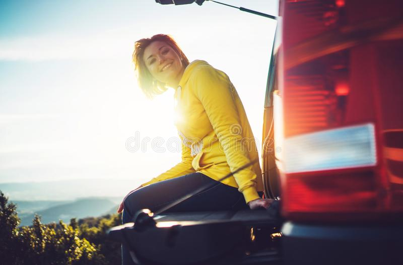 Den turist- handelsresanderesanden i bil på gräsplanöverkant på berget, ung flicka ler lyckligt mot bakgrundssolnedgång i bergHet arkivfoton