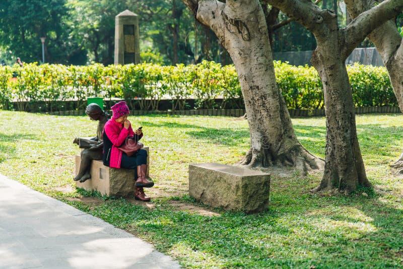 Den turist- kvinnan som sitter och ser på hennes telefon på kubstenplats i, parkerar arkivfoton
