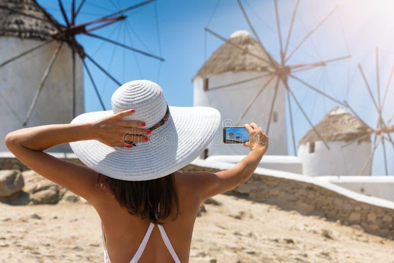 Den turist- kvinnan tar en bild av de berömda väderkvarnarna av Mykonos, arkivbild