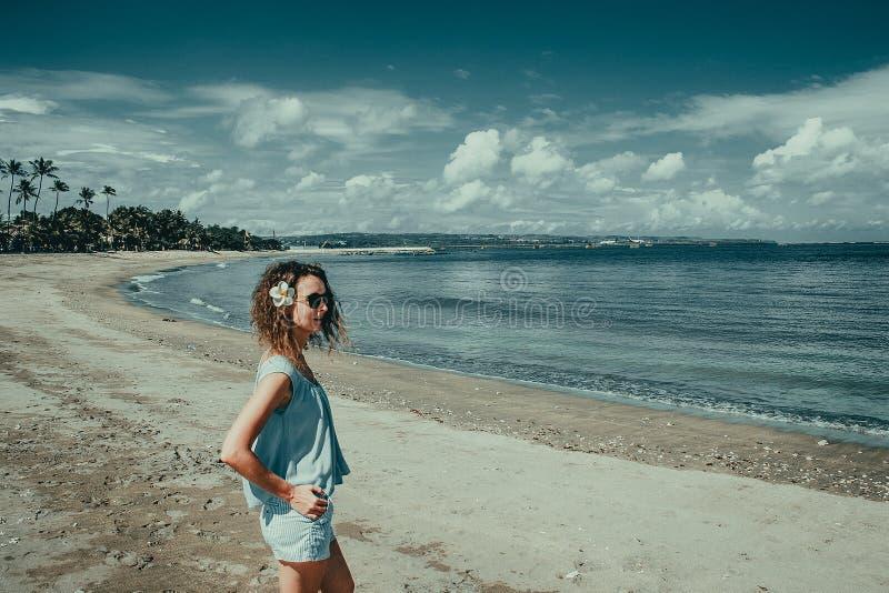 Den turist- kvinnan tycker om semester på den Kuta stranden Bali handelsresande Undersök det härliga Indonesien landskapet Folklo arkivbild