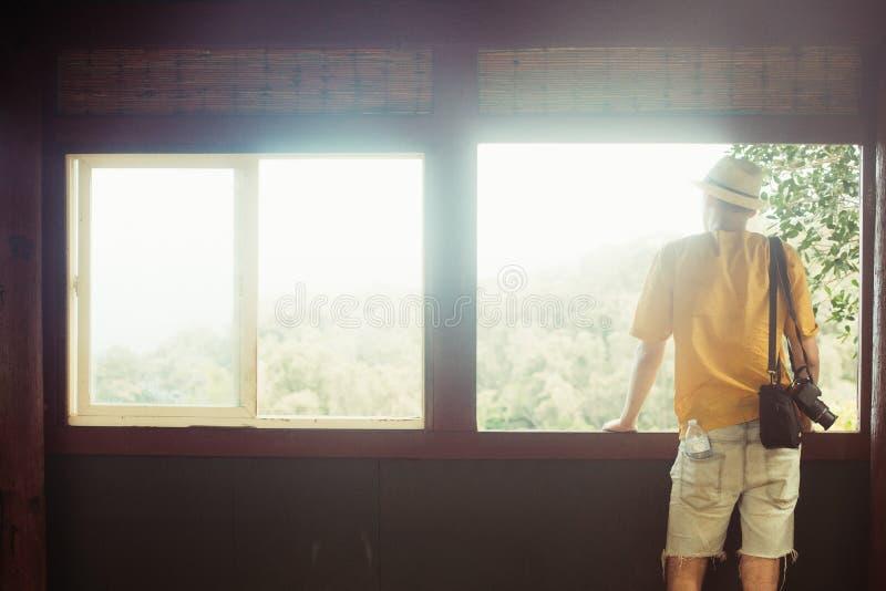 Den turist- mannen med en kamera på semester att tycka om förbiser solig skogsikt från fönsterbalkongen royaltyfri bild
