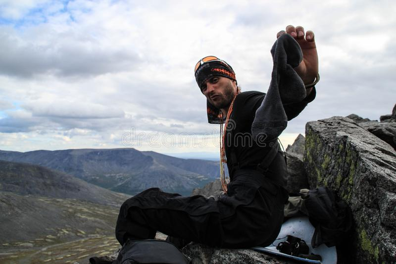 Den turist- unga mannen ändrar gamla stinky sockor under en vandring fotografering för bildbyråer