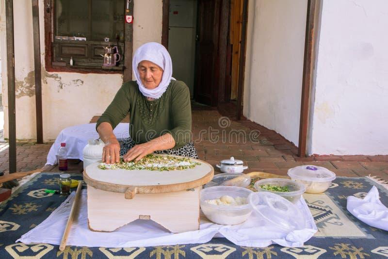 Den turkiska kvinnan gör en traditionell nationell maträtt - en bakad plan pannkaka Gozleme arkivbild