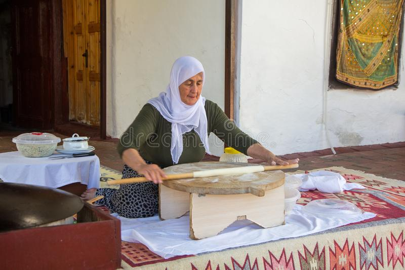 Den turkiska kvinnan gör en traditionell nationell maträtt - en bakad plan pannkaka Gozleme arkivfoton