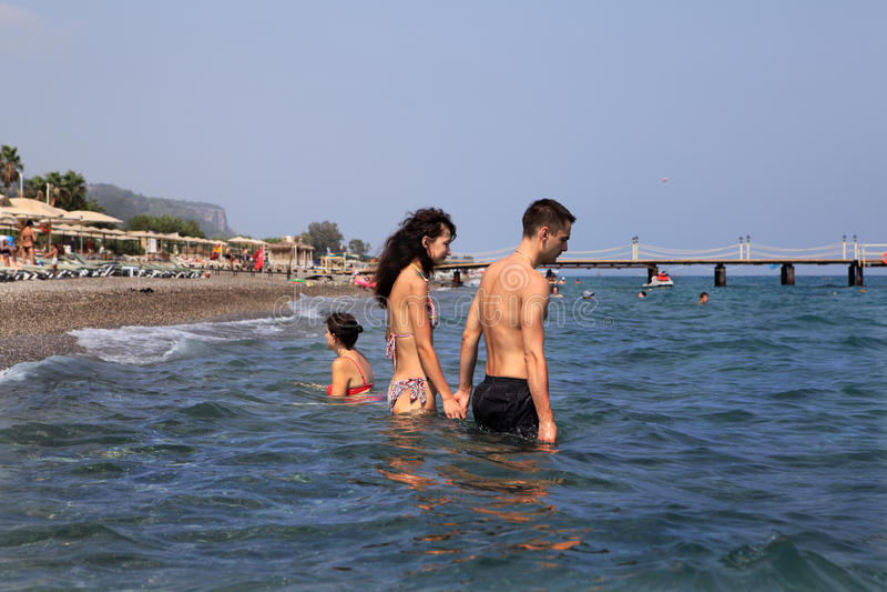 Den turkiska semesterorten, par går djupt in i havsvatteninnehavhänderna arkivbild