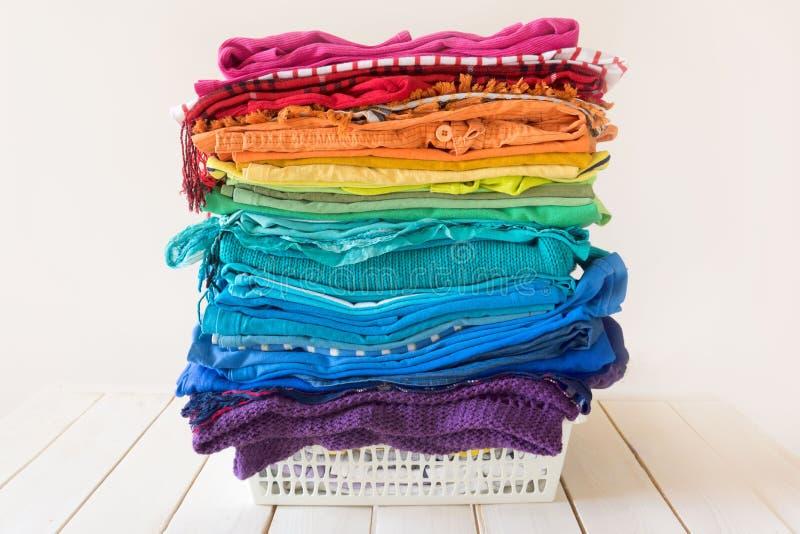Den tvättade tvätterit är i korgen Ljusa regnbågekläder är fotografering för bildbyråer