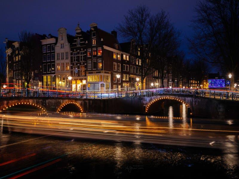 Den typiska amsterdam kanalplatsen med traditionella hus och ljusa slingor bildar fartyg på natten royaltyfri foto