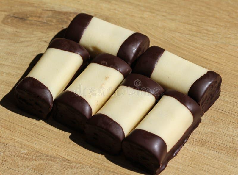 den typiska holländska söta kakan kallade & x22; mergpijpje& x22; täckt med vita marsipan, på en träbakgrund royaltyfria bilder