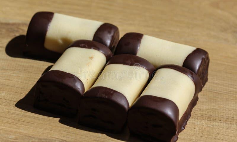 den typiska holländska söta kakan kallade & x22; mergpijpje& x22; täckt med vita marsipan, på en träbakgrund arkivfoton