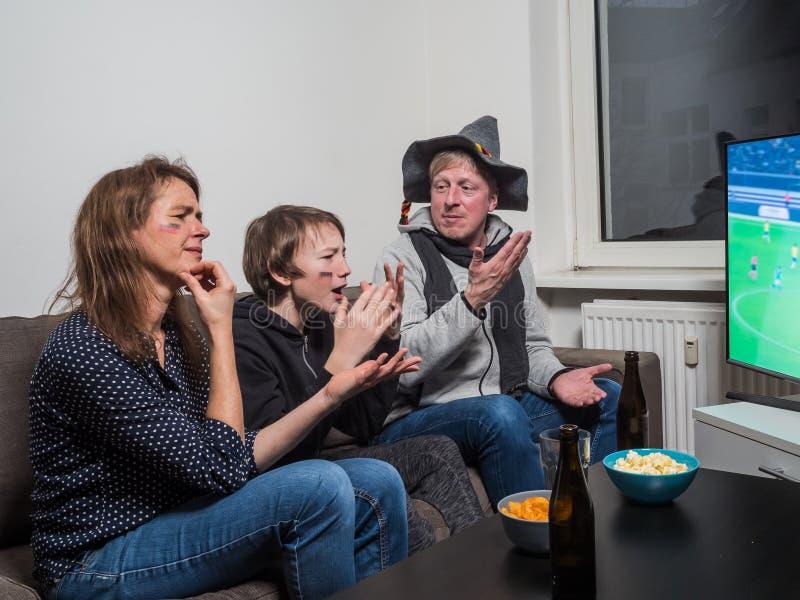 Den tyska familjen håller ögonen på fotbollvärldscupfotboll på tv royaltyfri bild