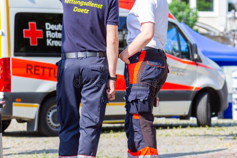 Den tyska kvinnliga personen med paramedicinsk utbildning står framme av en ambulansbil royaltyfria foton