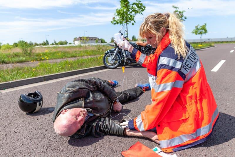 Den tyska personen med paramedicinsk utbildning hjälper en sårad motorcyklist arkivbild