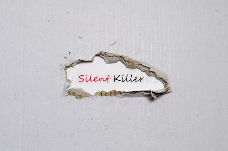 Den tysta mördaren för ord som visas bak sönderrivet papper royaltyfri foto