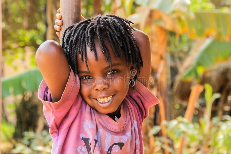 Den ugandiska afrikanska flickan med dreadlocks ler mycket gulligt, medan spela på gatan av Kampala förort royaltyfri fotografi