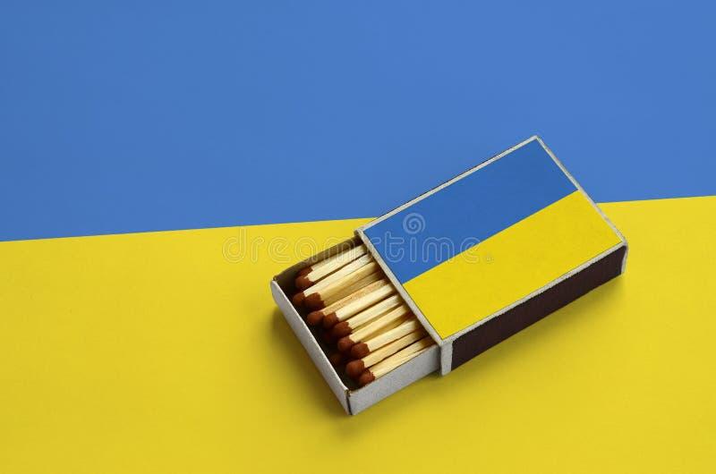 Den Ukraina flaggan visas i en öppen tändsticksask, som fylls med matcher och ligger på en stor flagga fotografering för bildbyråer