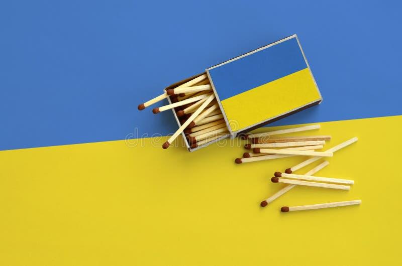 Den Ukraina flaggan visas på en öppen tändsticksask, som flera matcher faller från och lögner på en stor flagga arkivfoto