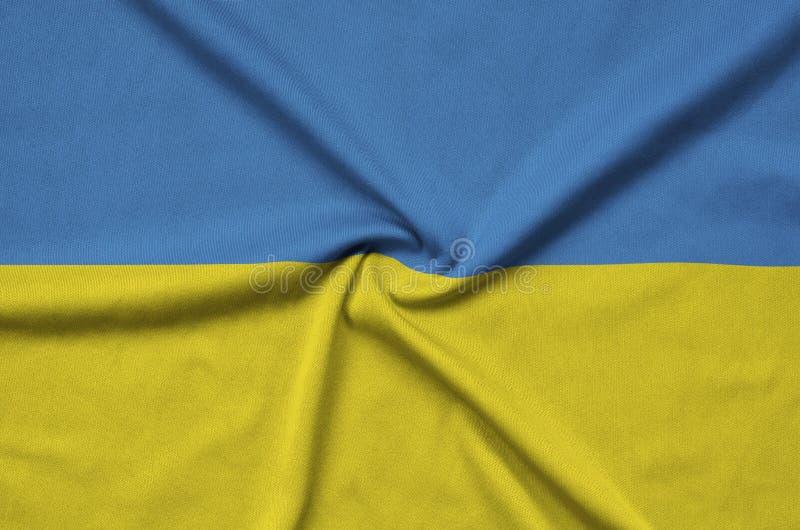 Den Ukraina flaggan visas på ett sporttorkduketyg med många veck Baner för sportlag royaltyfri fotografi