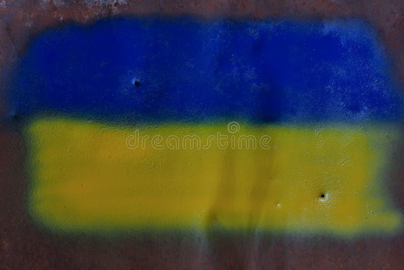 Den ukrainska flaggan som målas på ett ark av metall med, spårar av kulor royaltyfri foto