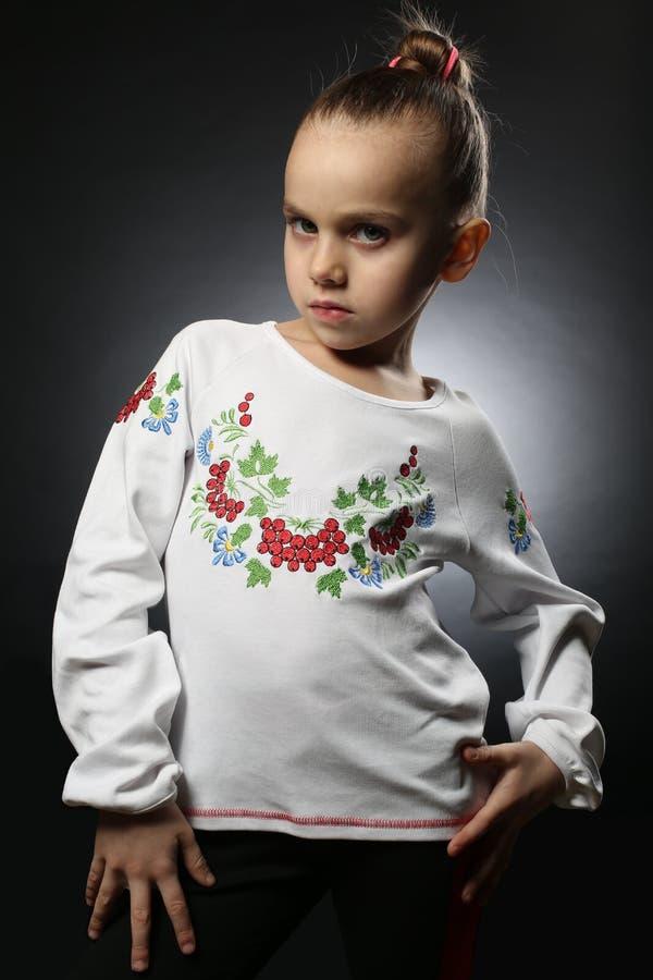 Den ukrainska flickan 5-9 gamla år, i en broderad skjorta med samlat hår visar säkert hans självständighet royaltyfri foto