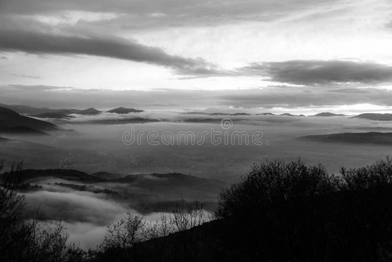 Den Umbria dalen i vinter fyllde vid mist på solnedgången, med att dyka upp kullar, dolde Foligno stadsljus och det härliga skott royaltyfri foto