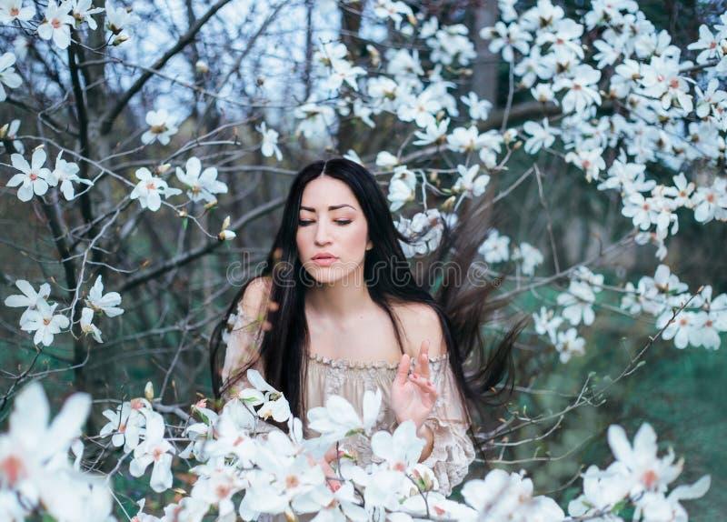 Den underbara attraktiva mörker-haired damen med ögon stängde ställningar i trädgården av att blomma magnolior hår flyger upp med fotografering för bildbyråer