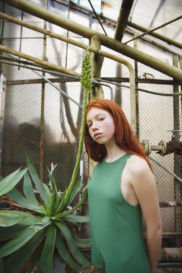 Den underbara flickan lutar på den gröna exotiska växten i grönska royaltyfri bild