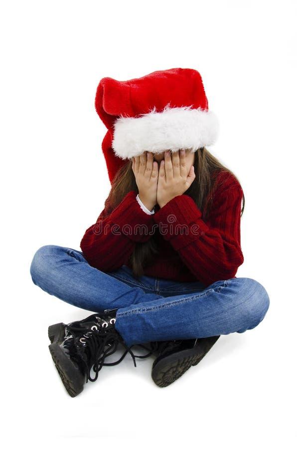 Den underbara lilla flickan över isolerad bakgrund med christmas-hatt med sorgligt uttryck som täcker ansiktet med händerna när h royaltyfria bilder
