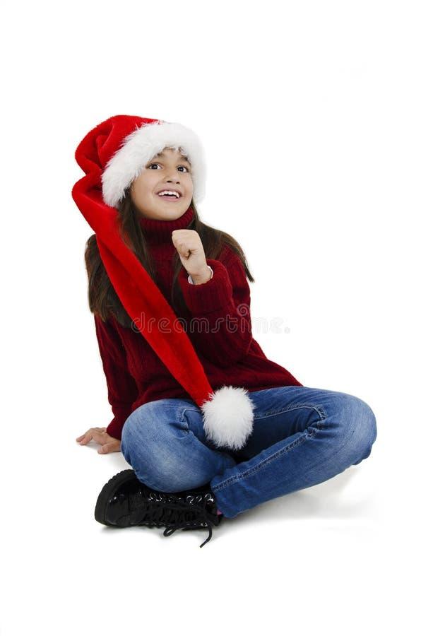 Den underbara lilla flickan i den röda julhatten som sitter på golvet och tittar upp Julflicka royaltyfri fotografi