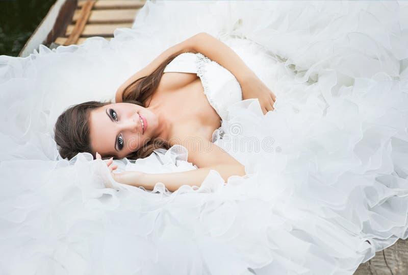 Den underbara mjuka bruden ligger i en bröllopsklänning royaltyfri fotografi