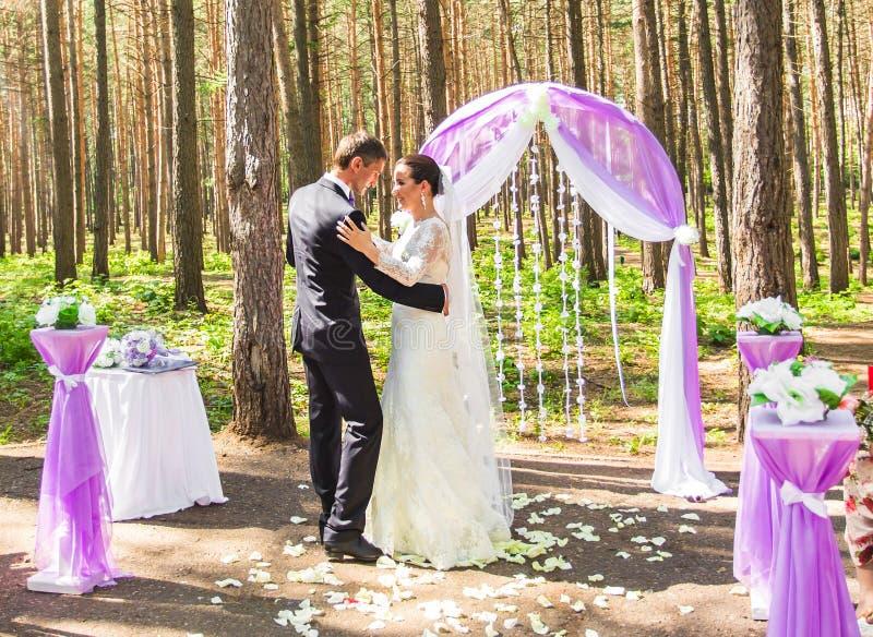 Den underbara stilfulla rika lyckliga brud- och brudgumdansen på en bröllopceremoni i gräsplanträdgård nära lilor välva sig med b royaltyfri fotografi