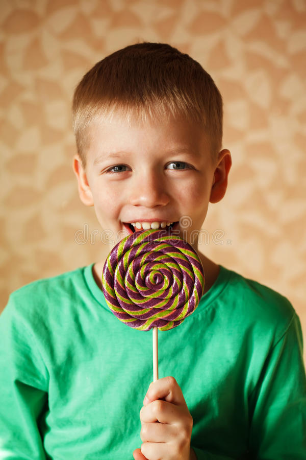 Den underhållande pojken äter den stora söta klubban royaltyfri foto