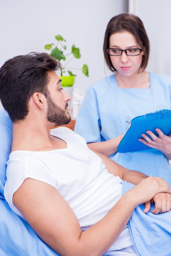 Den undersökande manliga patienten för kvinnadoktor i sjukhus fotografering för bildbyråer