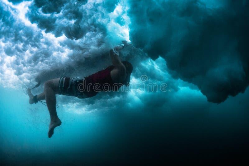 Den undervattens- sikten av surfaren som utför handling, namngav Sköldpadda Rol royaltyfria bilder
