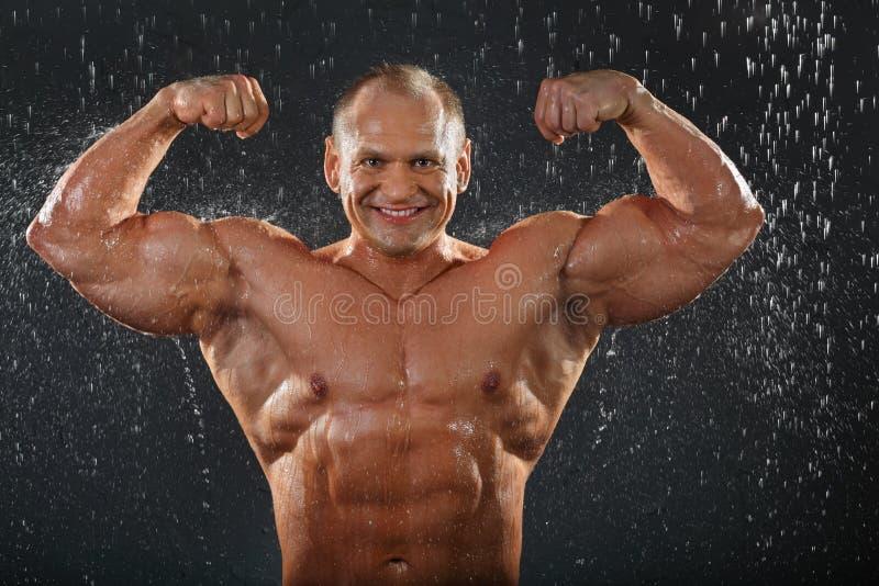 Den Undressed kroppsbyggaren visar muskler arkivbild
