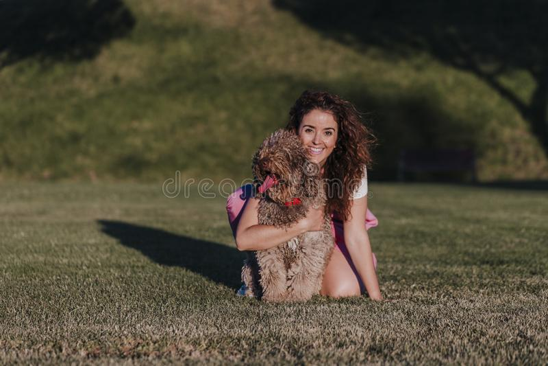 den unga ägarekvinnan med hennes bruna spanska vattenhund som har rolig det fria i, parkerar på solnedgången ?lska f?r djurbegrep royaltyfria foton
