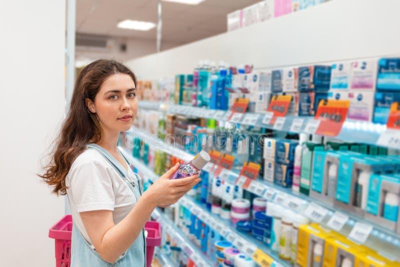 Den unga älskvärda kvinnan väljer munvatten Köp och försäljning av gods i lagret royaltyfri bild