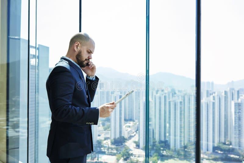 Den unga advokaten med den allvarliga framsidan och den digitala minnestavlan i hand talar på mobiltelefonen med klienten arkivfoton