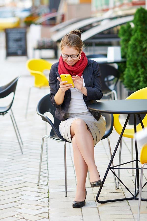Den unga affärskvinnan använder den smarta telefonen för arbete i kafé arkivbilder