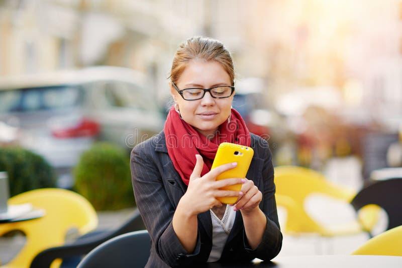 Den unga affärskvinnan använder den smarta telefonen för arbete i kafé arkivfoton