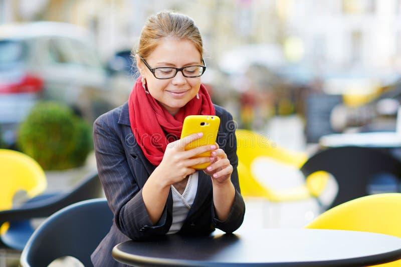 Den unga affärskvinnan använder den smarta telefonen för arbete i kafé royaltyfria foton