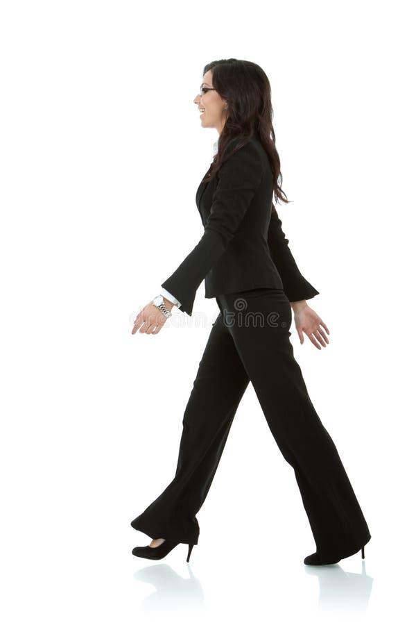 Den unga affärskvinnan går arkivbild