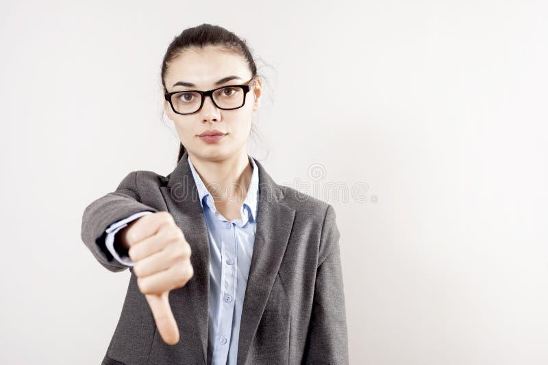 Den unga affärskvinnan ger tummar ner gest fotografering för bildbyråer