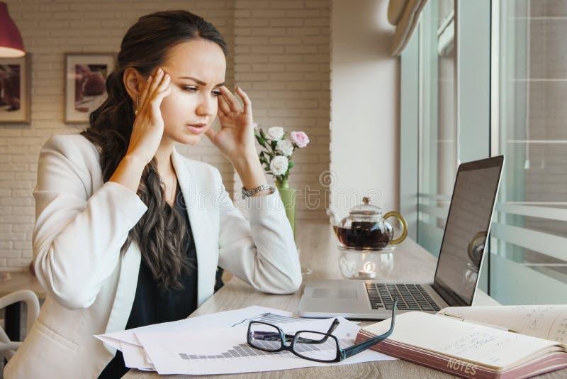 Den unga affärskvinnan har huvudvärk under arbete fotografering för bildbyråer