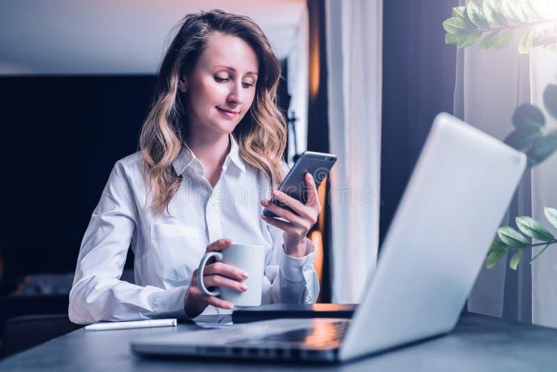 Den unga affärskvinnan i skjorta sitter i regeringsställning på tabellen framme av datoren, genom att använda smartphonen, blicka royaltyfri foto