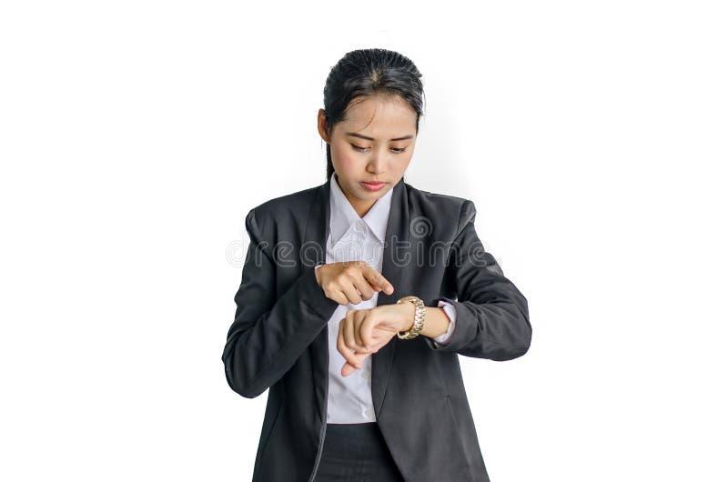 Den unga affärskvinnan kontrollerar tid på hennes armbandsur, tid, sent begrepp, royaltyfri foto