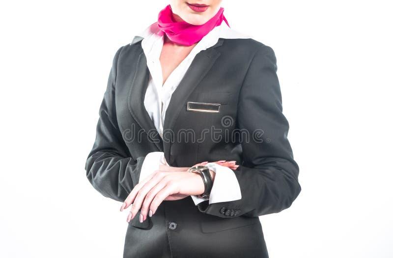 Den unga affärskvinnan kontrollerar tid på hennes armbandsur, tid, det sena begreppet, studioforsen som isoleras på vit royaltyfria bilder